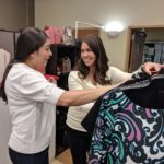 A Dress for Success volunteer helps a female veteran pick out an interview outfit