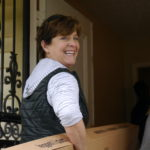 One of our ReNew founders loads items into a home for a domestic violence survivor.